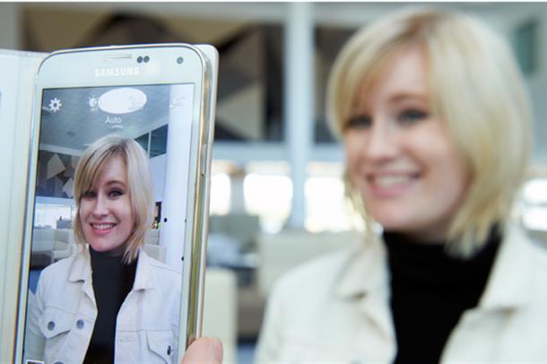 Bilde av dame som blir tatt bilde av med mobiltelefon